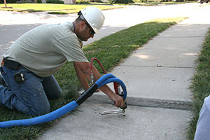 Technician raising sidewalk with PolyLevel