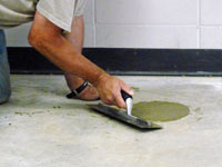 Repairing the cored holes in the concrete slab floor with fresh concrete and cleaning up the Roseville home.