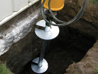 Installing a helical pier system in the earth around a foundation in Salinas