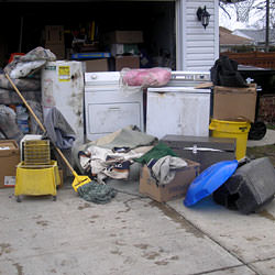Soaked, wet personal items sitting in a driveway, including a washer and dryer in Modesto.